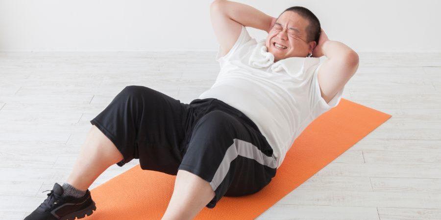 腹筋をする太った中年男性