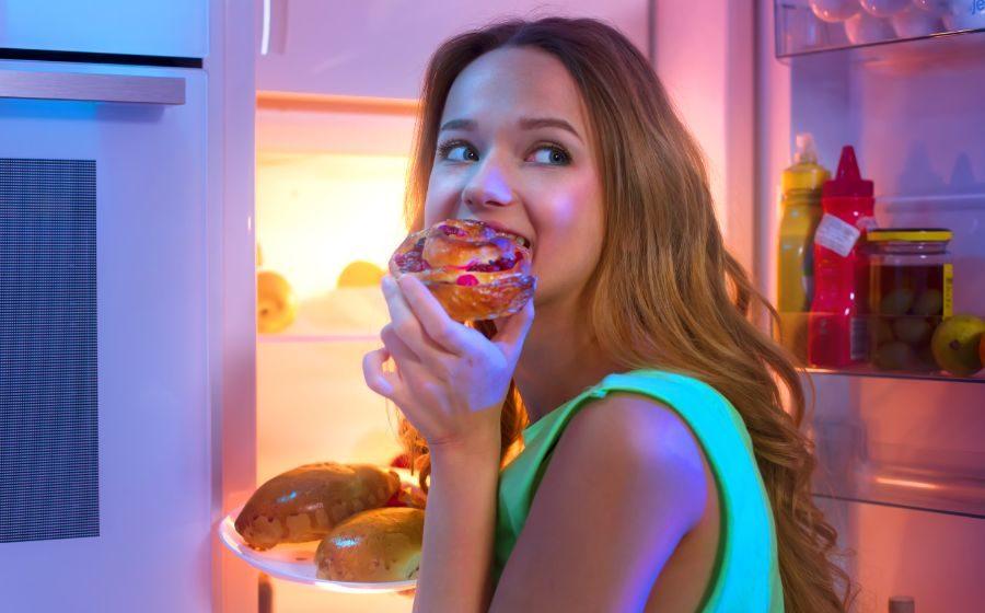冷蔵庫の前でドーナツを食べる女性