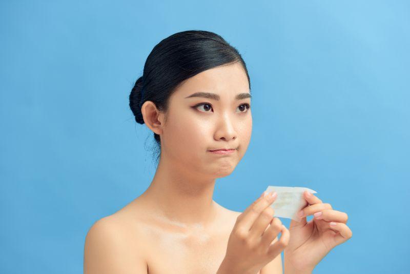 顔の脂をとる女性